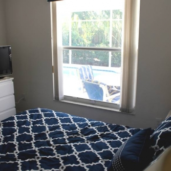 Guest Bedroom Has Plenty of Storage as Well as a View of the Pool